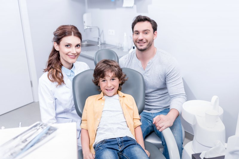 Smiling boy, father, and female dentist at dental office