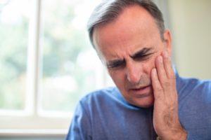 man with sore jaw needing an emergency dentist