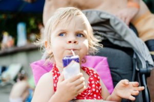 Suspicious little girl with cavities drinking a juice box