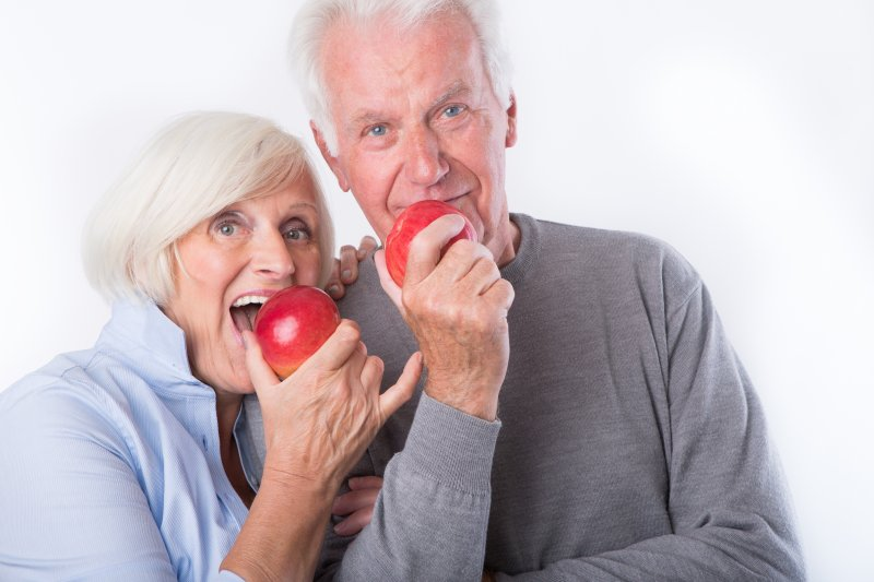 older couple with dentures eating apples